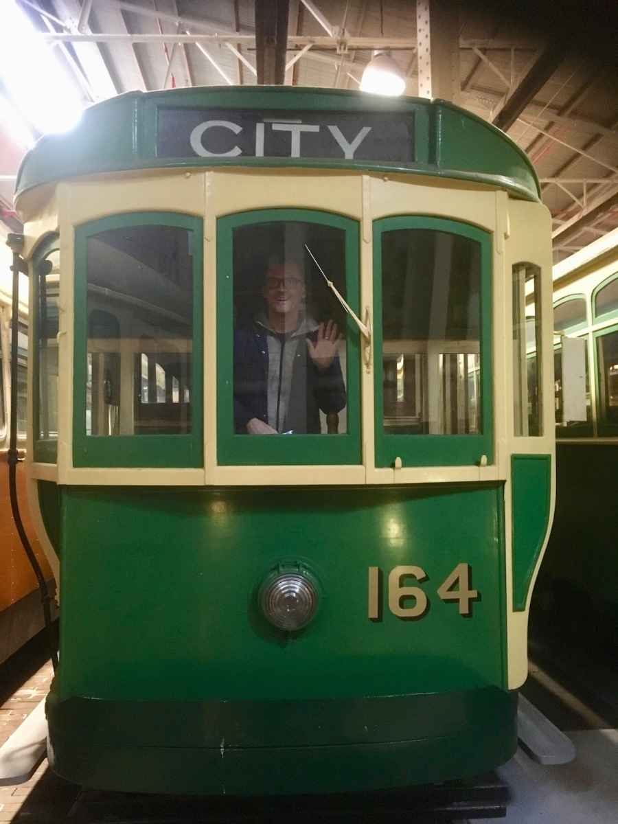 Man waving from drivers window of city tram at the Tram Museum, Hawthorn
