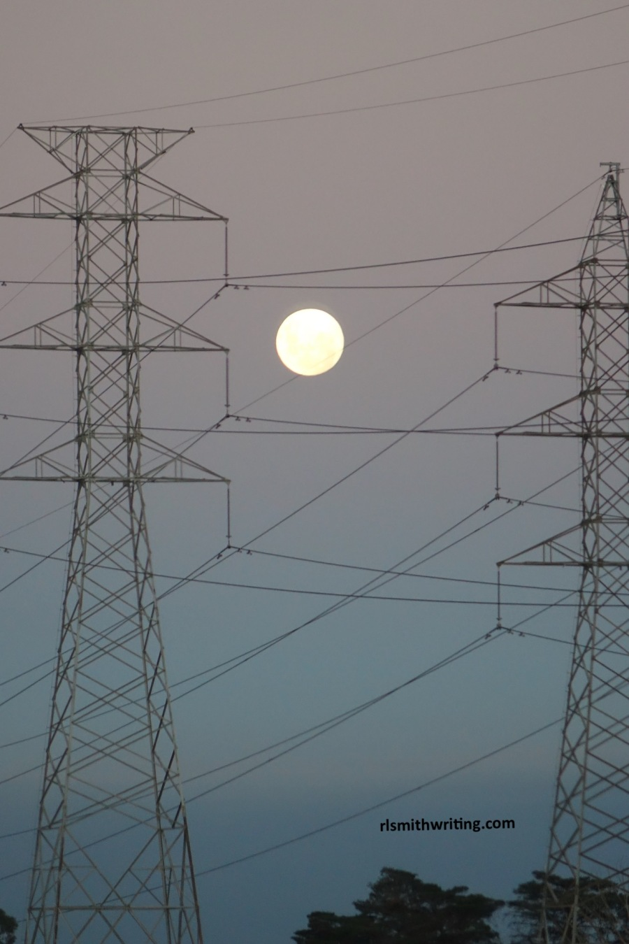 Full moon through electrical pylon wires