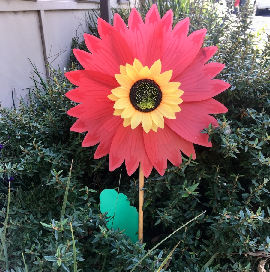 Large fake red and yellow sunflower in garden bed