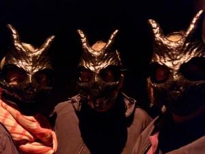 Three theatre goers dressed in dark cloaks and wearing black Donnie Darko masks