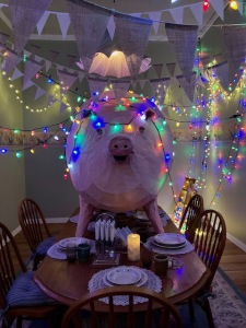 A room with a dining table set for a dinner party with fairy lights.  There is a very large replica pig standing in the middle of the table amongst the crockery