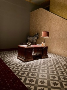 Theatre set showing office desk with light on a diamond motif carpet. There is a trussed up Zebra replica in one corner.