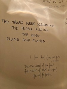 Text on theatre wall:  The trees were screaming the people fleeing the king flung and flayed  I fear that if my daughter  learns the true ordeal of the forest  and speaks it aloud at school she will be beaten